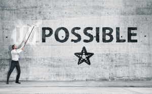 """A professional person removing the """" I M """" from the word Impossible, written on a gray wall"""